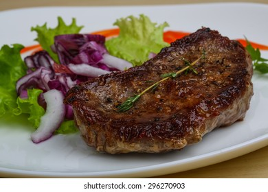 Grilled beef steak with onion and basil leaves