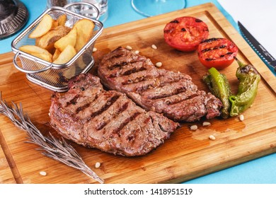 grilled beef steak with grilled pepper, onion rings and tomatoes. served with potato wedges and thyme. according to the Georgian recipe