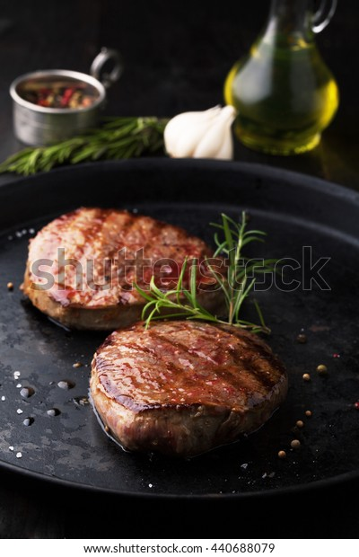 Grilled Beef steak with pepper, rosemary and salt on a dark background