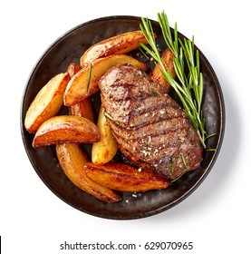 grilled beef steak and potatoes on plate isolated on white background, top view