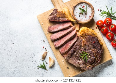 Grilled beef steak ribeye medium rare on wooden cutting board on white stone table. Top view with copy space.