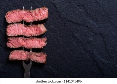 Grilled beef steak ribeye on meat fork sliced