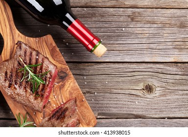 Grilled beef steak with rosemary, salt and pepper and red wine on wooden table. Top view with copy space. Rare roasted steak and bottle of wine