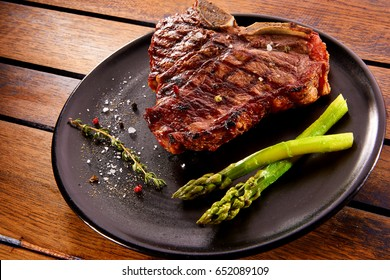 Grilled beef steak with rosemary. Grilled striploin sliced steak. Juicy thick grilled T-bone beef steak seasoned with rosemary fresh of the summer BBQ. Vegetables on a black plate with salt and pepper