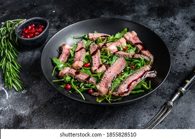 Grilled Beef Steak salad with arugula, pomegranate and greens vegetables. Black background. Top view