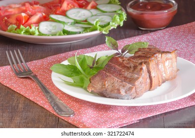 Grilled beef steak with salad and sauce on wooden table at white plate. Salad with tomatoes and cucumbers and sauce barbecue.
