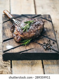 Grilled beef steak with salt, pepper and rosemary on meat cutting board on dark wooden background