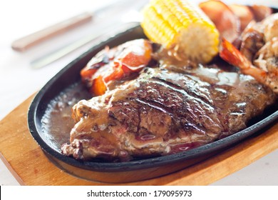 Grilled beef steak served on a hot sizzling plate with sweet corn, tomatoes, big prawns and brown sauce.