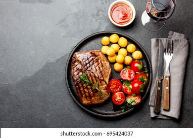 Grilled beef steak served on cast iron plate with tomato salad, potatoes balls and red wine. Barbecue, bbq meat beef tenderloin. Top view, slate background.