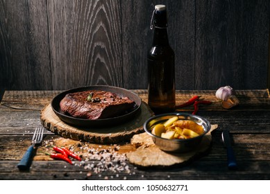 Grilled beef steak with spices on round board with potato fork , knife and craft beer