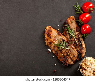 Grilled beef steak with spices on a black background with copy space.
