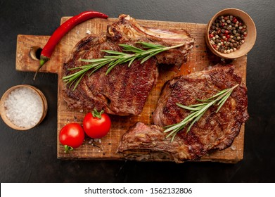 Grilled beef steak with spices on a stone background