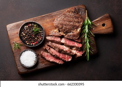 Grilled beef steak with spices on cutting board. Top view