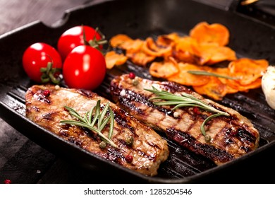 Grilled beef steak with tomato, garlic, potatoes, rosemary and spices on a pan and black background