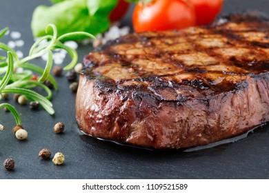 grilled beef steak with vegetables on gray slate background