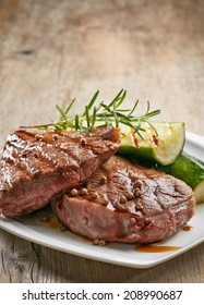 grilled beef steak and zucchini on white plate
