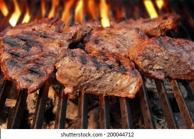 Grilled beef steaks and flaming grill in background
