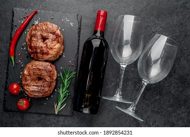 grilled beef steaks in the form of 8 and a bottle of wine, glasses on a stone background. 8 march celebration concept