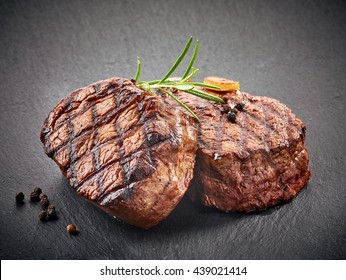grilled beef steaks with spices on black stone cutting board