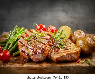 Grilled beef steaks and vegetables on wooden cutting board