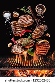 Grilled beef steaks with vegetables and spices fly over the blazing grill barbecue fire. Concept of flying food.