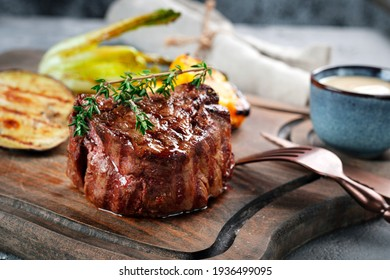 Grilled beef tenderloin steak on a wooden board with grilled vegetables. Filet Mignon recipe concept, selective focus