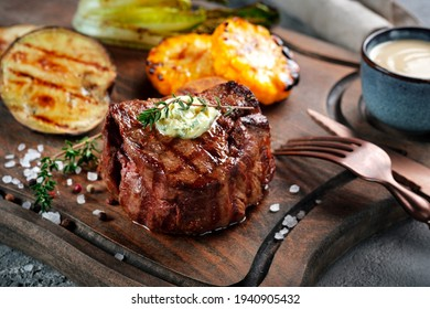 Grilled beef tenderloin steak on a wooden board with butter and thyme. Filet Mignon recipe with vegetables