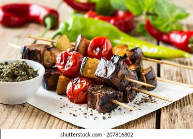 Grilled beef and vegetables shish kabobs on skewers with pesto sauce on wooden rustic table