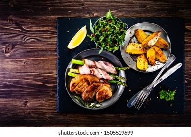 Grilled beefsteak with asparagus and baked potatoes on wooden background