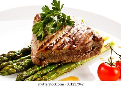 Grilled beefsteak and asparagus on white background