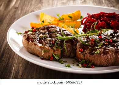 Grilled beefsteak with potatoes on wooden table