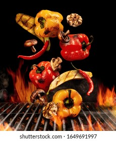 Grilled bell peppers, zucchini, champignons, chilli, halves of garlic are falling down on black background. Bbq grill, flaming fire charcoal. Close up