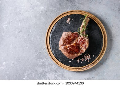 Grilled black angus beef tomahawk steak on bone served with salt, pepper and rosemary on round wooden slate cutting board over grey texture background. Top view, copy space.