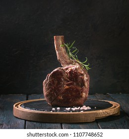 Grilled black angus beef tomahawk steak on bone served with salt, pepper and rosemary on round slate cutting board over dark wooden plank kitchen table. Copy space. Square image