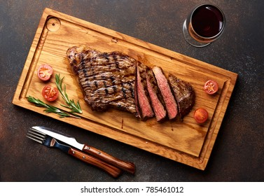 Grilled Black Angus Steak and a glass of red wine with tomatoes, rosemary on meat cutting board.