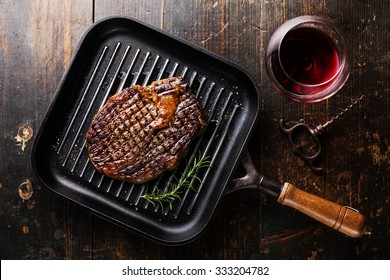 Grilled Black Angus Steak Ribeye on grill pan and red wine on wooden background