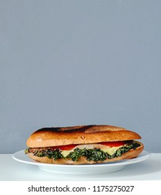 Grilled BLT baguette sandwich on white plate and plain backgroud with copy space for text. Shot in vertical view or portrait orientation. Suitable for book cover.