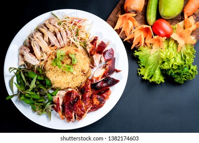 Grilled and boiled chicken rice decorated on white dish on black background