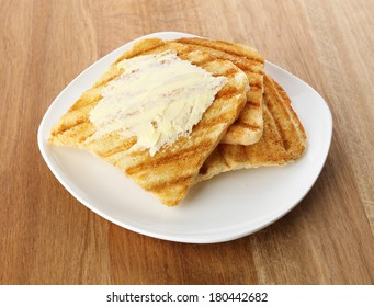Grilled bread with butter on wooden table