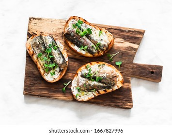 Grilled bread sardines micro greens sandwiches on a rustic cutting board on a light background, top view
