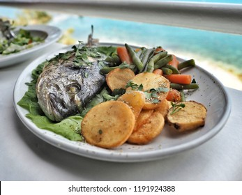 Grilled bream (dorado) with potatoes and fresh salad on the plate with sea on background. Close up.