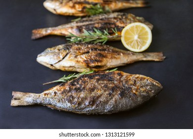 Grilled bream fish with herbs and spices on black background.