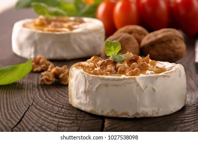 Grilled brie cheese with honey and nuts on old wooden background