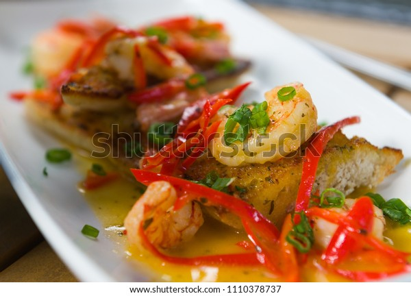 Grilled bruschetta with shrimps, white sauce and red pepper. decorated with fresh chives.