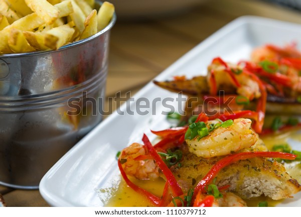 Grilled bruschetta with shrimps, white sauce and red pepper served with french fries.