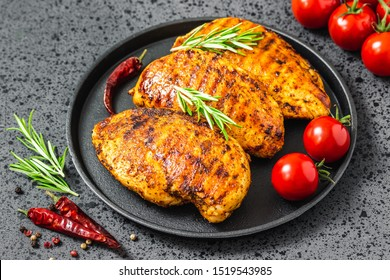 Grilled buffalo chicken breasts, cast iron skillet, dark background.