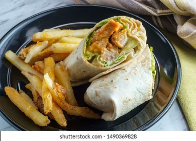 Grilled buffalo chicken sandwich wrap with romaine lettuce bleu cheese and fries