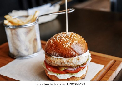 Grilled burger and french fries on wooden board