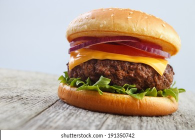 Grilled burger on wooden board with gray background