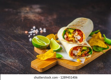 Grilled burritos wraps with chicken, beans, corn, tomatoes and avocado on a wooden board, dark background. Meat burrito, mexican food.